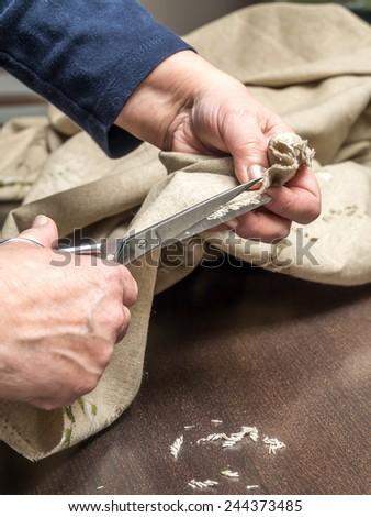 Closeup of senior woman's hands trimming linen border using scissors - stock photo