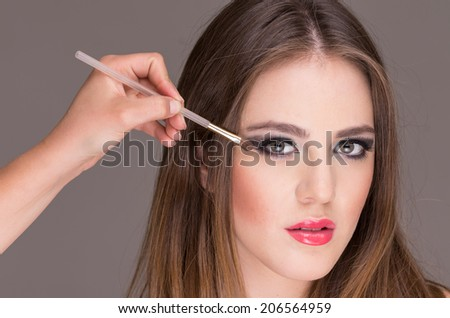closeup of sensual blond young woman getting makeup done in eyes - stock photo