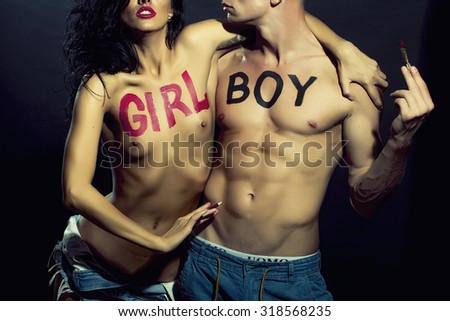 Closeup of sensual embracing pair of undressed man and lady with black boy and pink girl text on chest written by lipstick holding painting brush standing on studio background, horizontal picture - stock photo