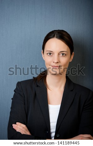 closeup of serious businesswoman with arms crossed against blue wall - stock photo