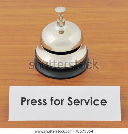 Closeup of service bell and sign on wooden desk
