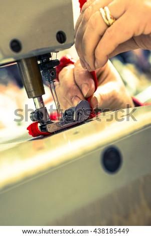 Closeup of sewing machine needles stitching a red ribbon - stock photo