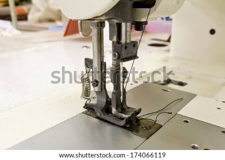 Closeup of sewing machine working part with leather and cloth
