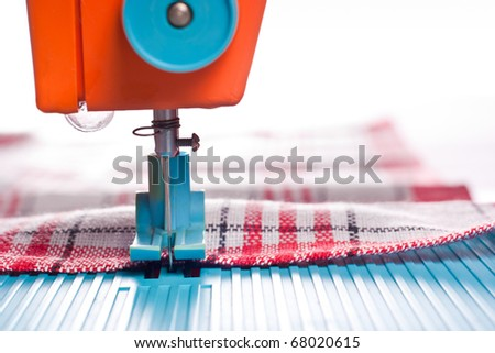 Closeup of sewing machine working part with red cloth - stock photo