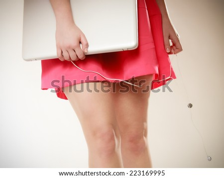 Closeup of sexy female legs and white computer laptop with headphones on pink. Girl listening to music. - stock photo