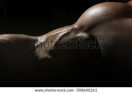 Closeup of sexy tan swollen muscular male biceps of young bodybuiding man with athlete wet strong body on black studio background, horizontal picture - stock photo