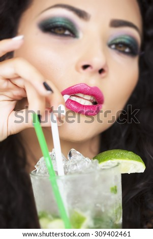 Closeup of sexy young brunette lady with curly hair and bright makeup drinking alcoholic mojito cocktail from mint soda light rum ice cubes and lime with straw, vertical picture - stock photo