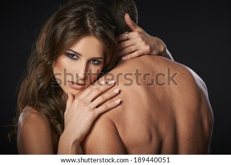 Closeup of sexy young couple embracing against black background - stock photo