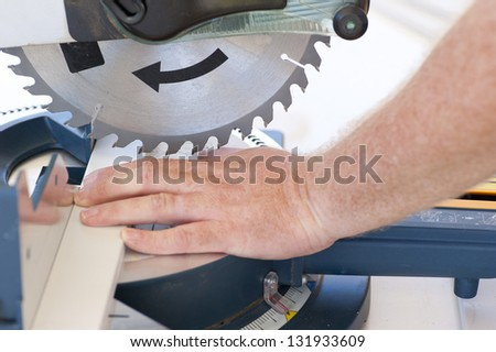 Closeup of sharp circular saw blade and hand of carpenter or worker, concept image safety and security at workplace. - stock photo