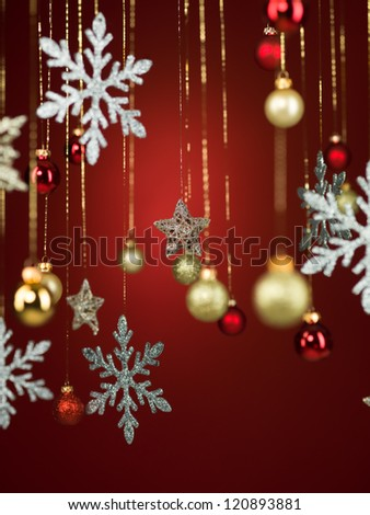 closeup of shiny christmas decorations hanging from golden threads on red background