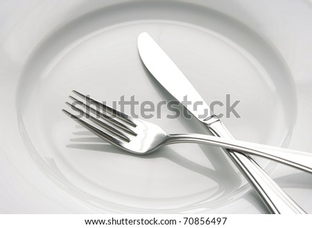 Closeup of shiny fork and knife on a white plate. - stock photo