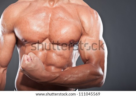 Closeup of shirtless muscled fitness man. Tough guy. Tanned skin. Studio shot isolated on grey background. - stock photo