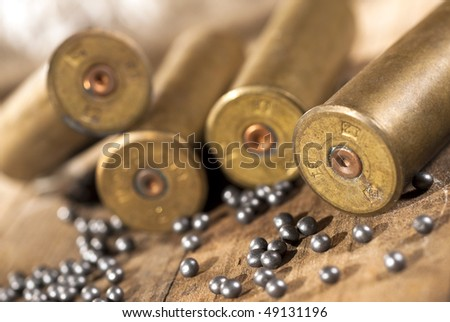 Closeup of shotgun shells and shot on wood background - stock photo