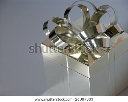 closeup of silver gift box and bow with copy space at left, shallow depth of field with focus on bow