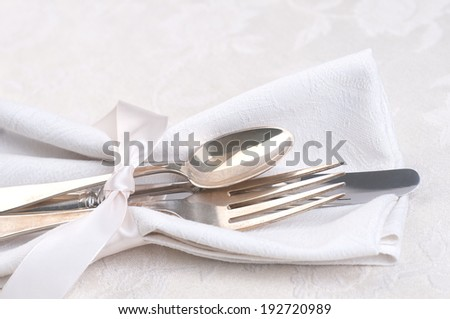 Closeup of Silverware tied in satin ribbon and a cloth napkin on cream white damask tablecloth from above.  Horizontal