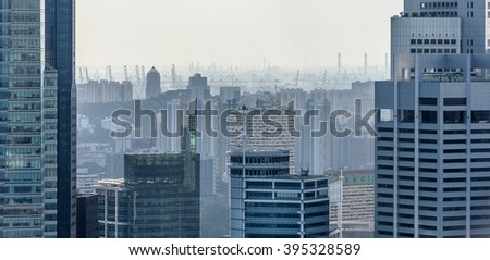 Closeup of Singapore downtown skyscrapers and Singapore port in a distance - stock photo