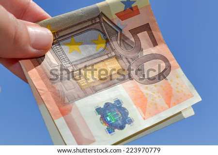 Closeup of single banknote of fifty euros with the sky as background - stock photo