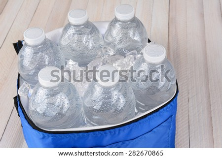 Closeup of six plastic water bottles and ice in a collapsible cooler on a white wood table. Horizontal format with copy space - stock photo