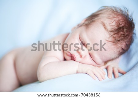 Closeup of sleeping baby lying on blue blanket with hands in a comfortable position