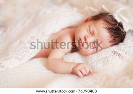 Closeup of sleeping baby lying on white blanket with hands in a comfortable position - stock photo