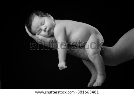 Closeup of sleeping newborn baby in father's hands on a black background