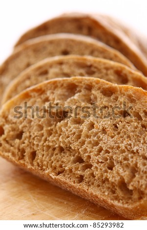 Closeup of sliced bread on a chopping board - stock photo