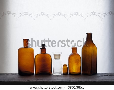 Closeup of small brown old glass bottles at windowsill against daylight - stock photo