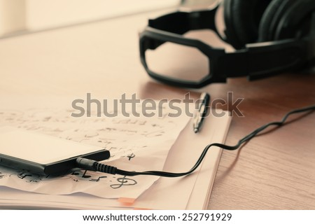 Closeup of smart phone with headphone on musical notes paper with shallow DOF evenly matched  on wooden desk   - stock photo