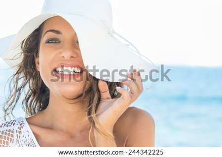 Closeup Of Smiling Beautiful Young Woman At Beach With Straw Hat - stock photo