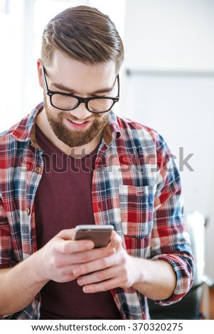 Closeup of smiling handsome bearded man in checkered shirt using mobile phone  - stock photo