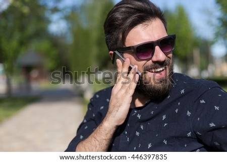 Closeup of smiling handsome bearded man in  shirt using mobile phone - stock photo