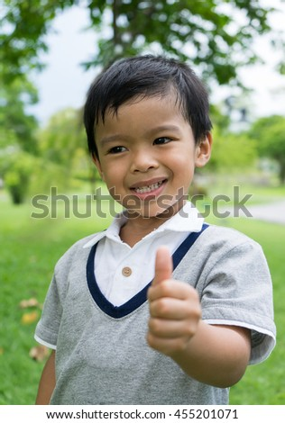 Closeup of smiling little asia boy showing thumb up gesture - stock photo