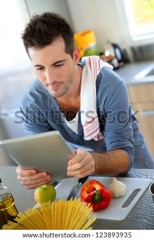 Closeup of smiling man in kitchen using tablet - stock photo