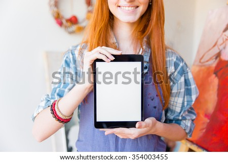 Closeup of smiling pretty young woman artist showing blank screen tablet in drawing class - stock photo