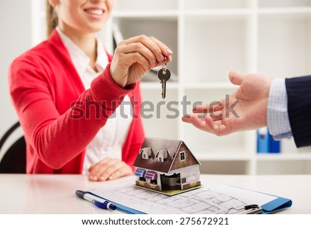 Closeup of smiling woman realtor giving key of new apartment to client. Female house agent sitting at the desk with house miniature and plan.   - stock photo