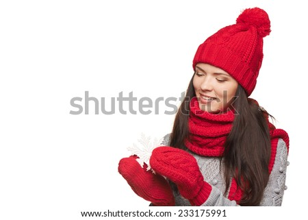 Closeup of smiling woman wearing red winter hat, scarf and mittens holding white big snowflake and looking at it, over white background - stock photo