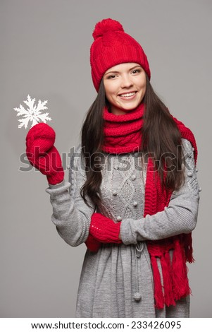 Closeup of smiling woman wearing red winter hat, scarf and mittens holding white big snowflake over gray background