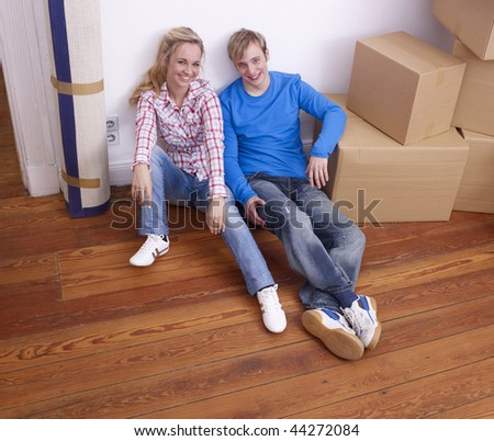 Closeup of smiling young couple sat on wooden floor next to pile of large cardboard boxes. - stock photo