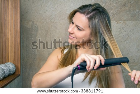 Closeup of smiling young woman straightening her hair with a straightener in the bathroom. Health and beauty concept. - stock photo