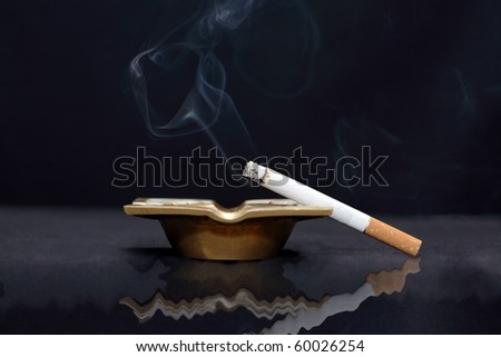 Closeup of smoking cigarette lying on old bronze ash-tray on dark background