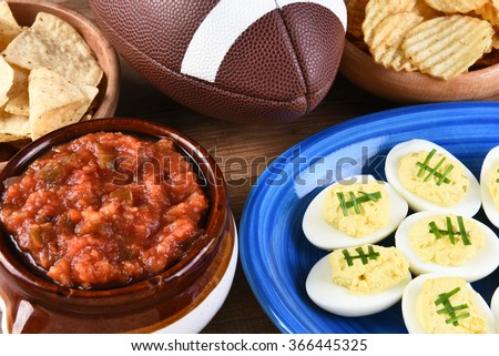 Closeup of snacks for watching a football game, chips, salsa and deviled eggs. Great for Super Bowl or Playoff themed projects. - stock photo