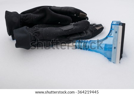 Closeup of snow and ice car cleaner with winter gloves on the snow - stock photo