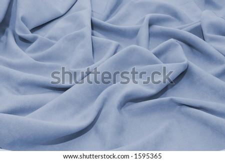 closeup of soft blue fabric to make a garment - stock photo