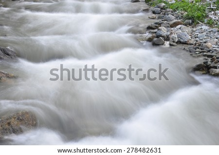 Closeup of Soft water cascading over mountain rocks./Soft Cascading water over mossy rocks - stock photo