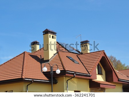 Closeup of solar panel on red tiled house roof with skylights, chimney and roof window. - stock photo