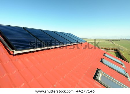 Closeup of solar panels on red roof with small windows. Blue sky and green field in background. - stock photo