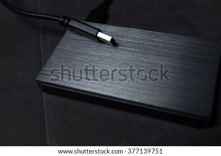 Closeup of solid aluminium casing external hard drive on textured gray background - stock photo