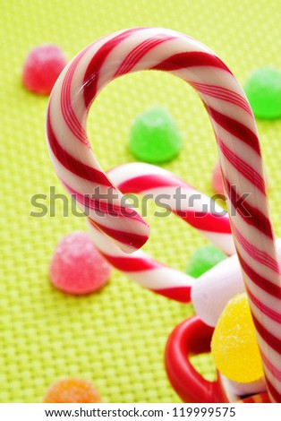 closeup of some candy canes and gumdrops on a woven background - stock photo