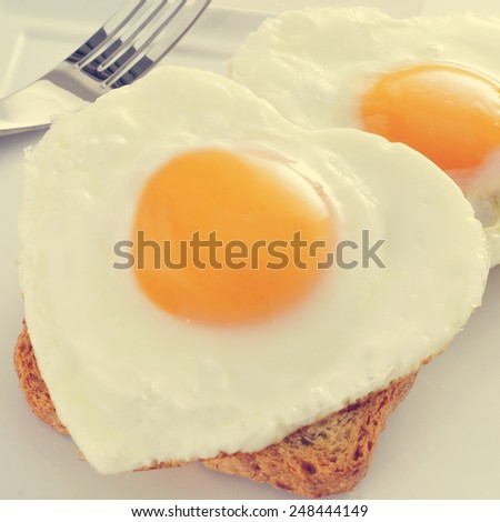 closeup of some heart-shaped fried eggs served on toasts, with a filter effect - stock photo