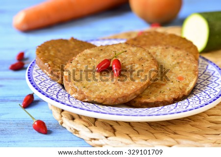 closeup of some raw veggie burgers in a plate on a blue wooden table, with some vegetables in the background - stock photo